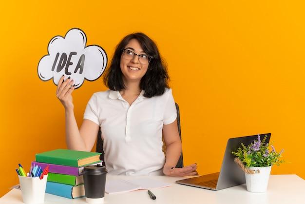 Молодая улыбающаяся симпатичная кавказская школьница в очках сидит за столом со школьными инструментами и держит знак идеи, глядя вверх изолированно на оранжевом пространстве с копией пространства