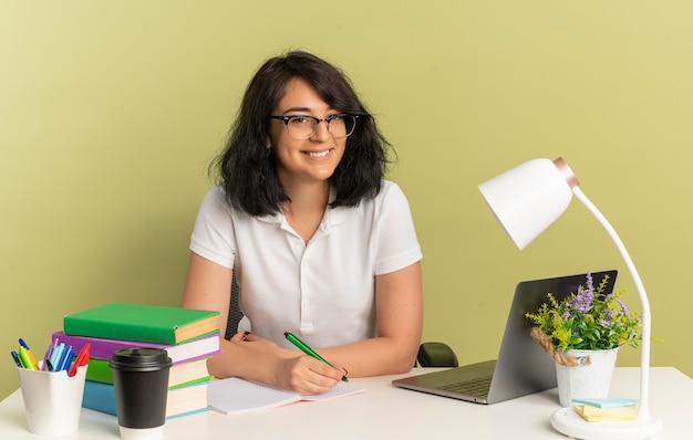 안경을 쓰고 젊은 웃는 예쁜 백인 여학생 학교 도구와 책상에 앉아 펜 복사 공간이 녹색 공간에 고립 된 보유