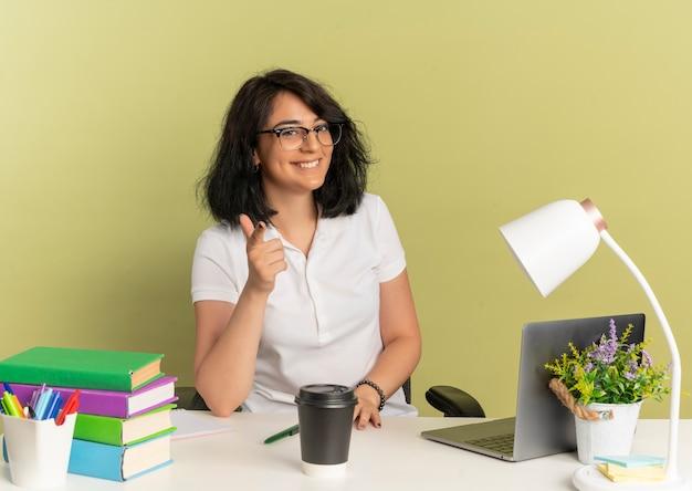 안경을 쓰고 젊은 웃는 예쁜 백인 여학생 학교 도구 외모와 복사 공간이 녹색 공간에 고립 된 카메라에 포인트와 책상에 앉아