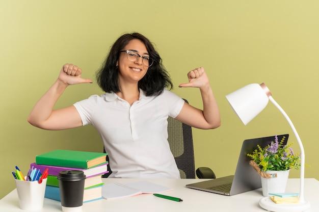 안경을 쓰고 젊은 웃는 예쁜 백인 여학생은 복사 공간이 녹색 공간에 고립 된 자신에 학교 도구 포인트와 책상에 앉아
