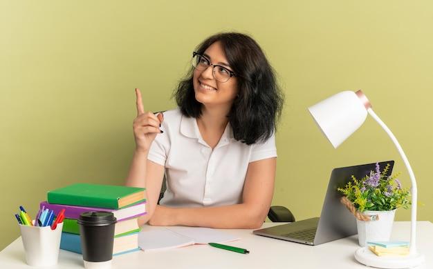안경을 쓰고 젊은 웃는 예쁜 백인 여학생은 학교 도구 포인트 복사 공간이 녹색 공간에 고립 된 측면을보고 책상에 앉아
