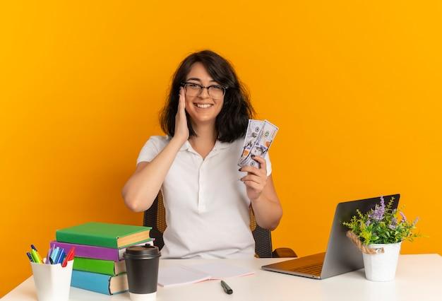 Молодая улыбающаяся симпатичная кавказская школьница в очках сидит за столом со школьными инструментами, кладет руку на лицо, держит деньги, изолированные на оранжевом пространстве с копией пространства
