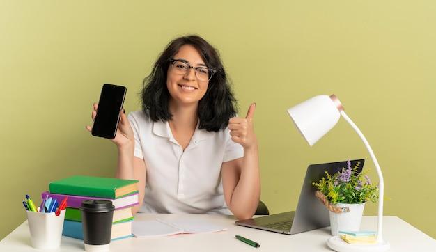 안경을 쓰고 젊은 웃는 예쁜 백인 여학생은 학교 도구 엄지 손가락으로 책상에 앉아서 복사 공간이있는 녹색 공간에 고립 된 전화를 보유하고 있습니다.