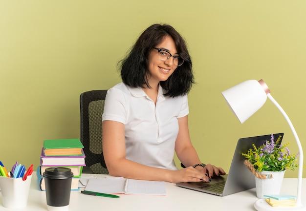 안경을 쓰고 젊은 웃는 예쁜 백인 여학생은 복사 공간이 녹색 공간에 고립 된 노트북을 사용하는 학교 도구와 책상에 앉아