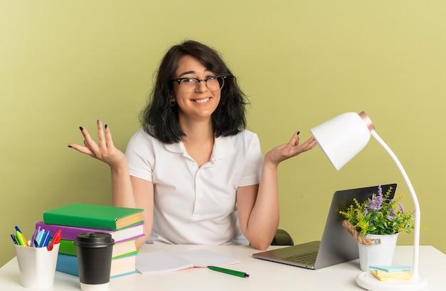 안경을 쓰고 젊은 웃는 예쁜 백인 여학생은 복사 공간이있는 녹색 공간에 고립 된 학교 도구로 책상에 제기 손으로 앉아있다.
