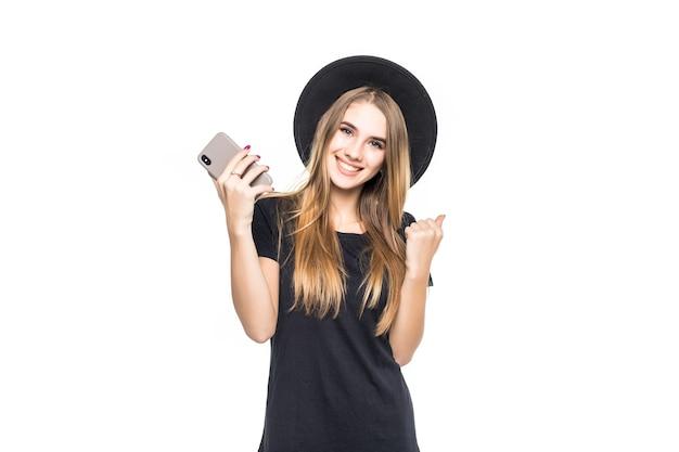 若い笑顔のかわいい女の子、白い背景で隔離の携帯電話