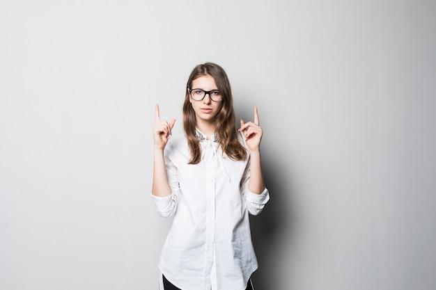 La giovane ragazza graziosa sorridente con gli occhiali si è vestita in maglietta bianca dell'ufficio rigoroso sta davanti al muro bianco