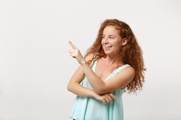 白い壁の背景、スタジオの肖像画に分離されたポーズでカジュアルな明るい服を着た若い笑顔のかわいい赤毛の女性の女の子。人々のライフスタイルの概念。コピースペースをモックアップします。人差し指を脇に向けます。