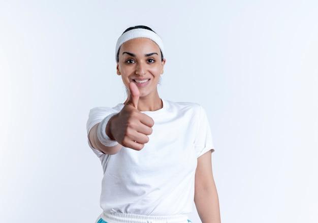 Pollici da portare della fascia e dei braccialetti da portare della donna abbastanza sportiva sorridente dei giovani in su isolato su spazio bianco con lo spazio della copia