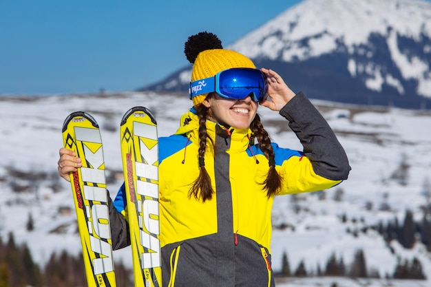 Young smiling pretty woman holding ski. mountains on background. winter travel. copy space