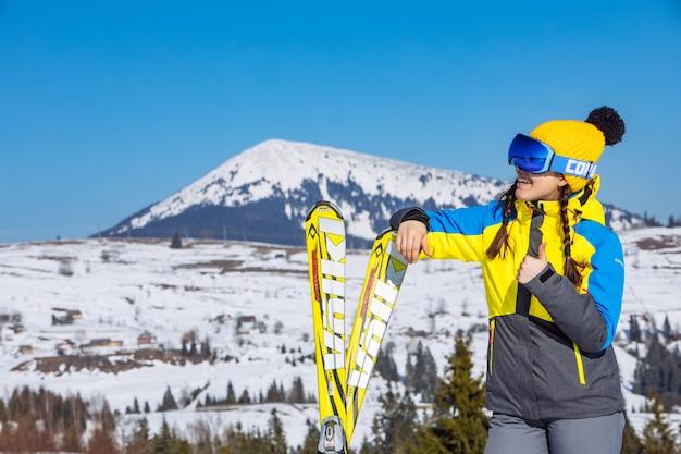 Молодой улыбается красивая женщина, держащая лыжи. горы на фоне. зимние путешествия. копировать пространство