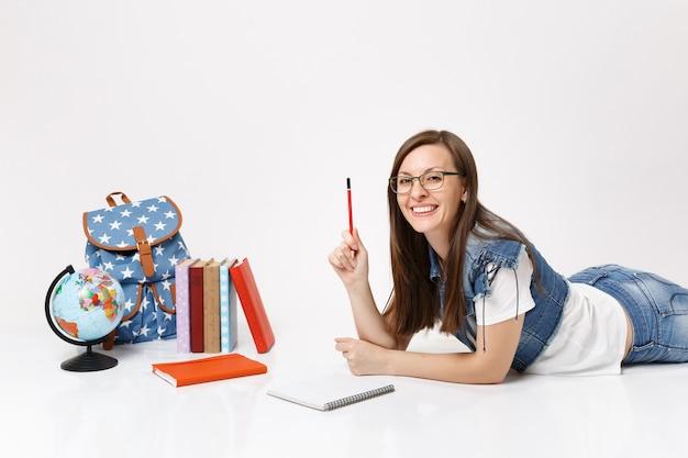 Giovane studentessa sorridente carina in abiti di jeans, occhiali con taccuino a matita sdraiato vicino al globo, zaino, libri scolastici isolati