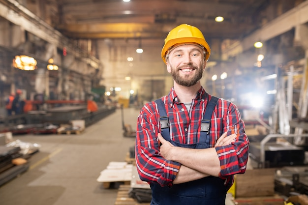 Young smiling professional in overalls and protective helmet posing inside large industry plant