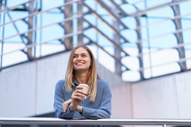 그녀의 전체 작업 하루 동안 커피 브레이크를 데 젊은 웃는 전문 여자. 그녀는 휴식을 취하고 음료를 즐기면서 비즈니스 빌딩 근처 야외에서 종이컵을 들고 있습니다.