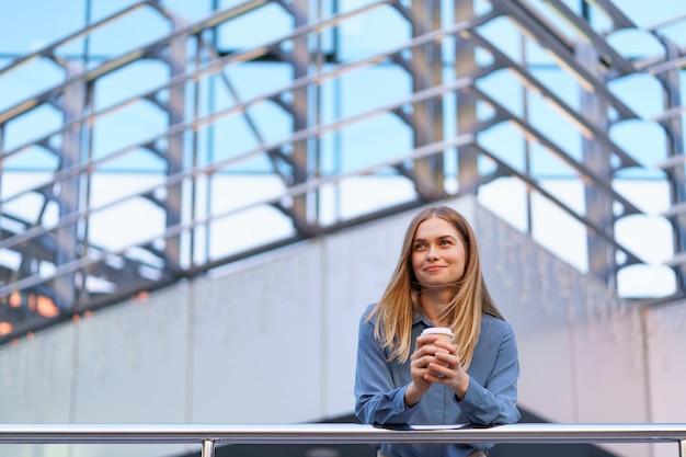 彼女の完全な稼働日の間にコーヒーブレークを持つ若い笑顔専門職の女性。彼女はリラックスして彼女の飲み物を楽しんでいる間、ビジネスビルの近くの屋外に紙コップを持っています。