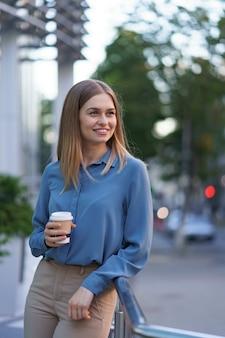 Молодая улыбающаяся профессиональная женщина, имеющая перерыв на кофе в течение ее полного рабочего дня. она держит бумажный стаканчик на открытом воздухе возле бизнес-здания, расслабляясь и наслаждаясь напитком.