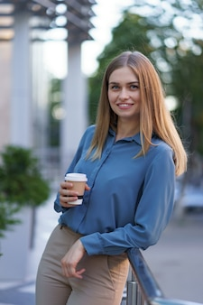 Young smiling professional woman having a coffee break during her full working day. she holds a paper cup outdoors near the business building while relaxing and enjoying her beverage.