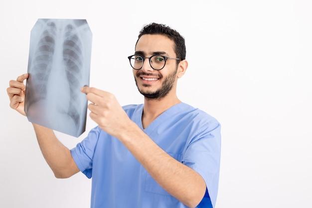 Молодой улыбающийся рентгенолог в синей форме держит рентгеновское изображение перед собой, глядя на вас