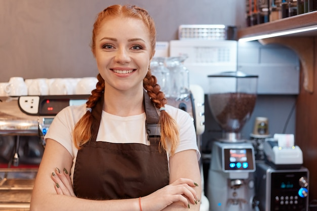 コーヒーショップのバーに立っている若い笑顔の赤い髪のバリスタ