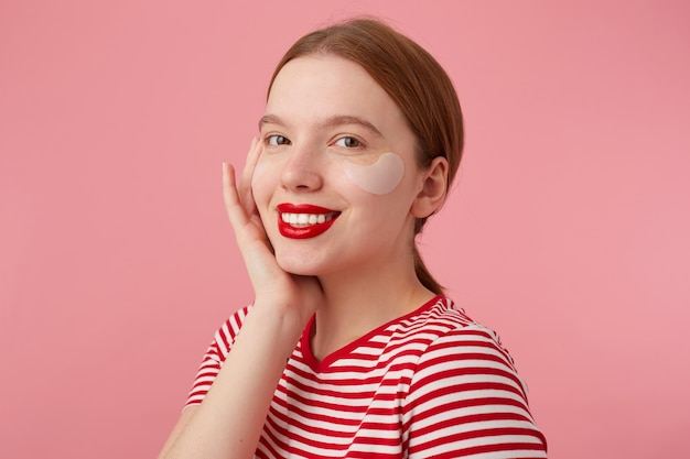 Young smiling red-haired girl with red lips and with patches under the eyes, wears in a red striped t-shirt, touches the cheek, stands and enjoying free time for skin care.