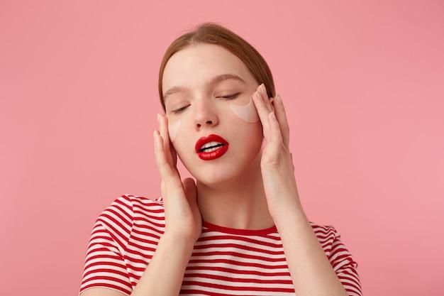 Giovane donna sorridente dai capelli rossi con labbra rosse indossa una maglietta a righe rosse, con macchie sotto gli occhi, con gli occhi chiusi massaggia le tempie e gode del tempo libero per la cura di sé