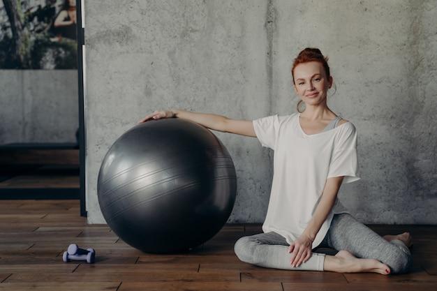 젊은 미소 빨간 머리 여성은 큰 운동 필라테스 fitball과 함께 포즈를 취하는 동안 피트니스 스튜디오의 회색 벽에 바닥에 앉아 훈련 후 휴식을 취합니다. 건강하고 활동적인 라이프 스타일 개념