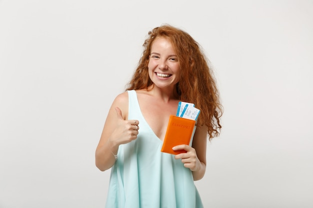 캐주얼 가벼운 옷을 입고 젊은 웃는 빨간 머리 여자 소녀는 흰색 배경에 고립 된 포즈. 사람들이 라이프 스타일 개념입니다. 복사 공간을 비웃습니다. 여권, 탑승권, 티켓을 들고 엄지손가락을 치켜들고 있습니다.