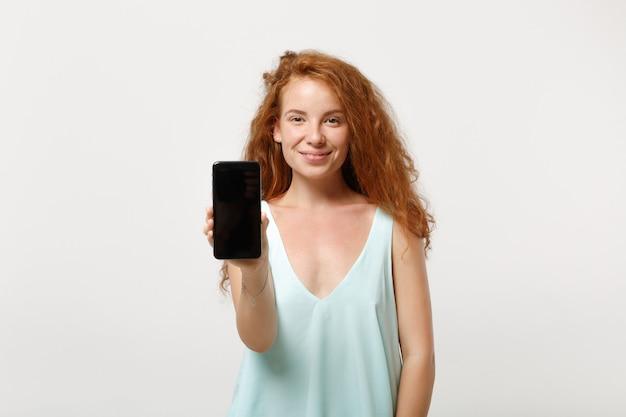 白い背景、スタジオの肖像画に分離されたポーズでカジュアルな明るい服を着た若い笑顔の赤毛の女性の女の子。人々のライフスタイルの概念。コピースペースをモックアップします。空白の空の画面で携帯電話を保持します。