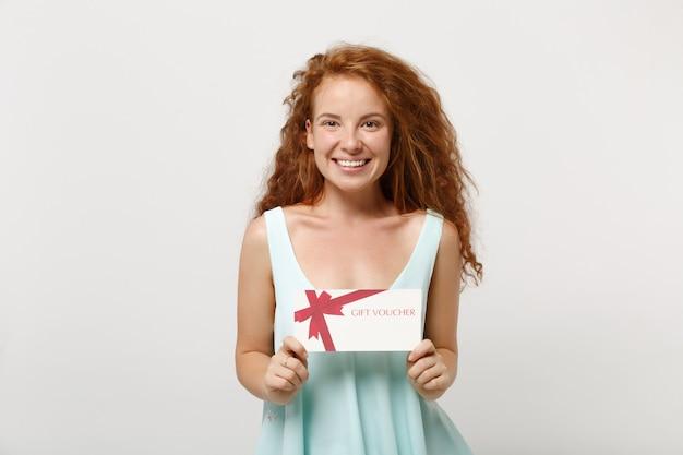 白い壁の背景、スタジオの肖像画に分離されたポーズでカジュアルな明るい服を着た若い笑顔の赤毛の女性の女の子。人々のライフスタイルの概念。コピースペースをモックアップします。手にギフト券を持っています。