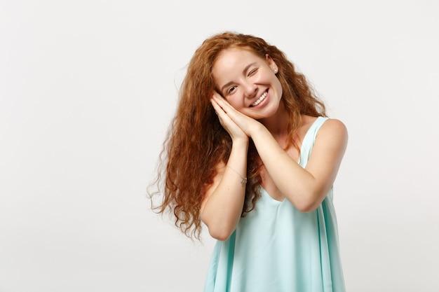 スタジオで白い背景に分離されたポーズのカジュアルな明るい服を着た若い笑顔の赤毛の女性。人々の誠実な感情のライフスタイルの概念。コピースペースをモックアップします。手を組んで頬の下で寝ます。