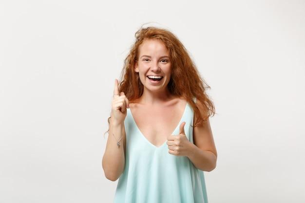 白い背景で隔離のポーズのカジュアルな明るい服を着た若い笑顔の赤毛の女性。人々のライフスタイルの概念。コピースペースをモックアップします。人差し指を上に向けて素晴らしい新しいアイデアを持ち、親指を立てます。