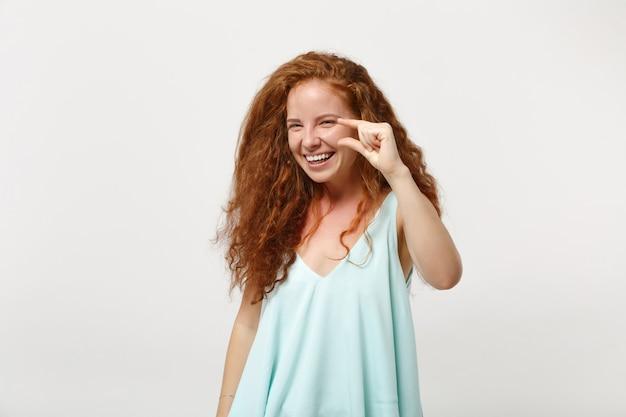 白い壁の背景のスタジオの肖像画に分離されたポーズをとってカジュアルな明るい服を着た若い笑顔の赤毛の女性。人々のライフスタイルの概念。コピースペースをモックアップします。ワークスペースでサイズを示すジェスチャー。