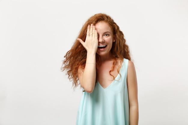 白い壁の背景のスタジオの肖像画に分離されたポーズをとってカジュアルな明るい服を着た若い笑顔の赤毛の女性。人々の誠実な感情のライフスタイルの概念。コピースペースをモックアップします。手で顔を覆う。