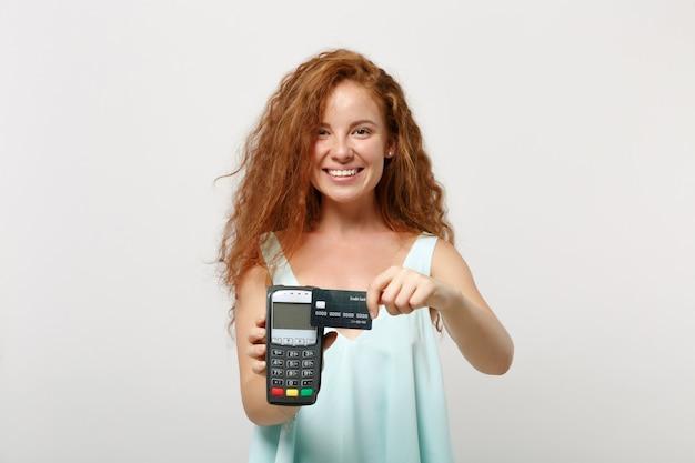 젊은 웃는 빨간 머리 여자에 고립 된 흰색 배경 포즈. 사람들이 라이프 스타일 개념입니다. 복사 공간을 비웃습니다. 처리할 무선 현대 은행 결제 단말기를 들고 신용 카드 결제를 획득합니다.