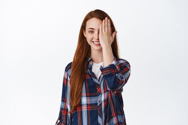 白地に格子縞のシャツに立っている長い赤い髪の若い笑顔の赤毛の女性