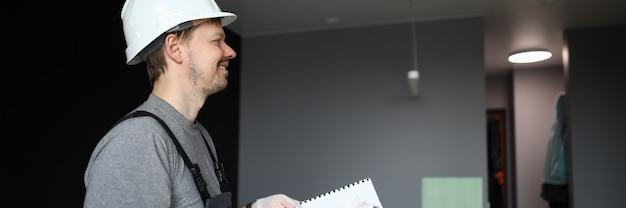 空のフラットに立っていると手で建設計画を保持している若い笑顔修理工