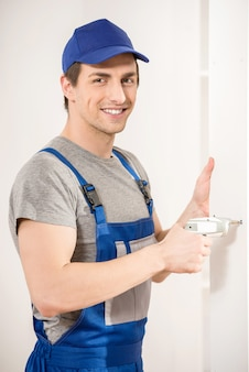 Young smiling repairman using hand drill at home interior.