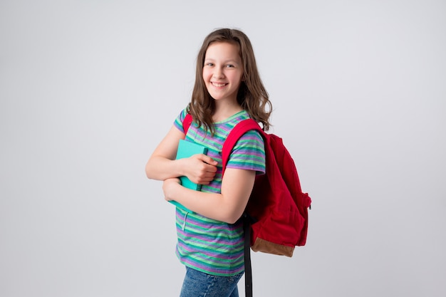 Young smiling schoolchild with backpack on her shoulders and notebook