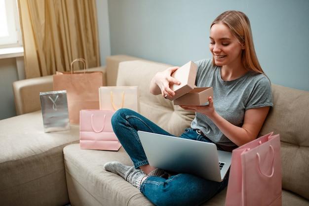 Молодая улыбающаяся покупательница распаковывает свою посылку и просматривает, заказывает и доставляет через интернет