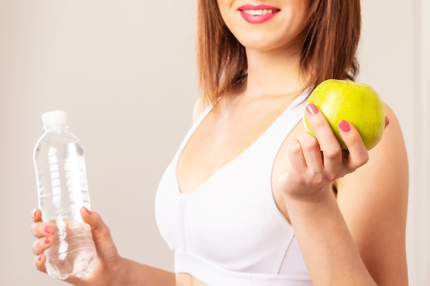Young smiling slim woman in white top holding a bottle of water and an apple.