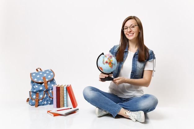 分離されたバックパックの教科書の近くに座って地理を学ぶ世界の地球を保持している眼鏡の若い笑顔のスマートな女性の学生