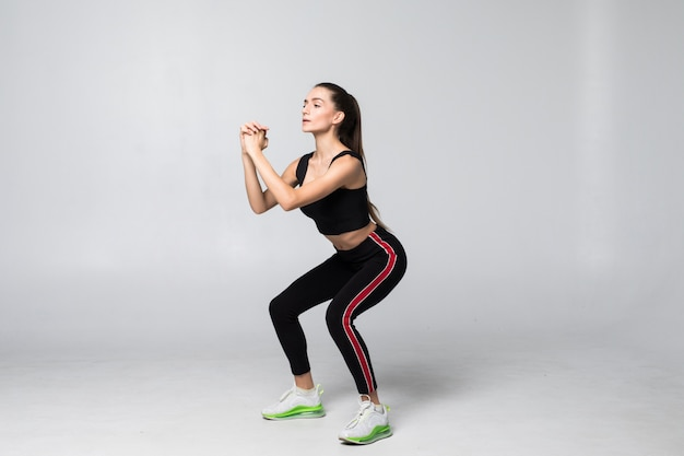 Young smiling sport woman doing squats on gray wall