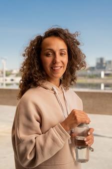 도시 환경에서 카메라 앞에 서있는 동안 야외 운동 후 물을 마시고 activewear에 젊은 웃는 운동가