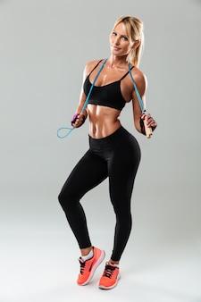 Молодая улыбающаяся спортсменка позирует со скакалкой