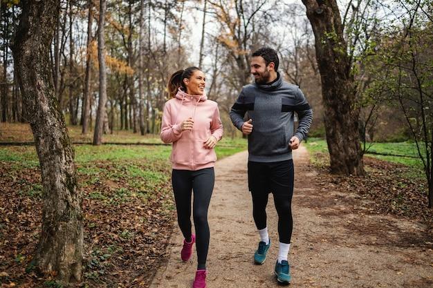秋の森の中を走り、マラソンの準備をしている健康的な習慣を持つ若い笑顔のスポーツウーマン。