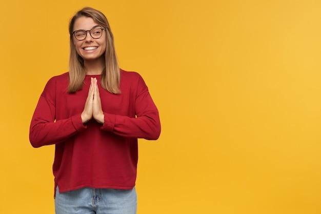 Giovane studentessa sorridente, tiene insieme il palmo della mano in posizione di preghiera, guarda da parte e fa l'occhiolino, indossa occhiali alla moda