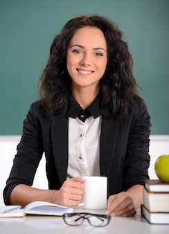 Young smiling student or teacher at the blackboard.