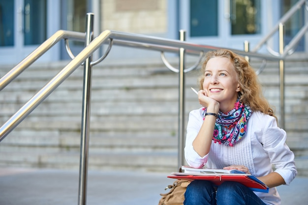 Young smiling student woman writing and reading book on stairs of university or college, preparing for exams.