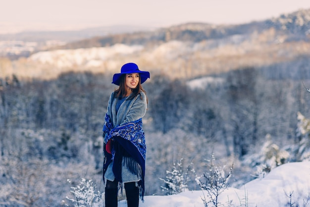 Young smiling stylish woman in blue hat and scarf walking in the park