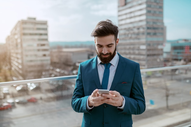 Young smiling successful bearded caucasian businessman in formal wear standing on the rooftop